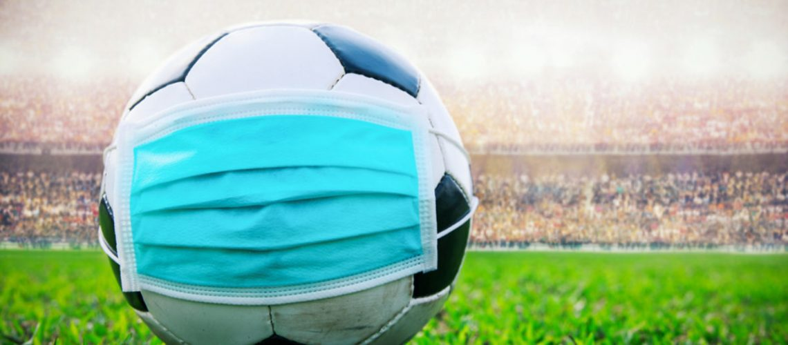 soccer ball with medical mask in the stadium. All event of soccer pause break. covid-19 spreading outbreak